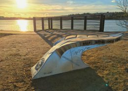 sunsets over the Plym Estuary with a giant leaf bench by the waters side
