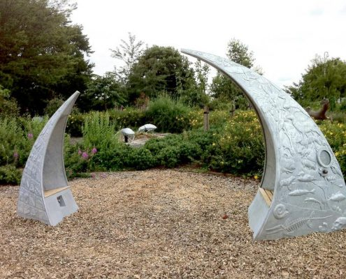 Milton Keynes School two metal arched seat with metal relief imagery of local heritage. Mad by Thrussells