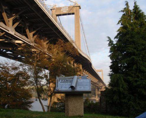 Beneath a large suspension bridge is a sculptural drawing board sculpture which celebrates the bridge designers. Made by Thrussells. Public Art Cornwall