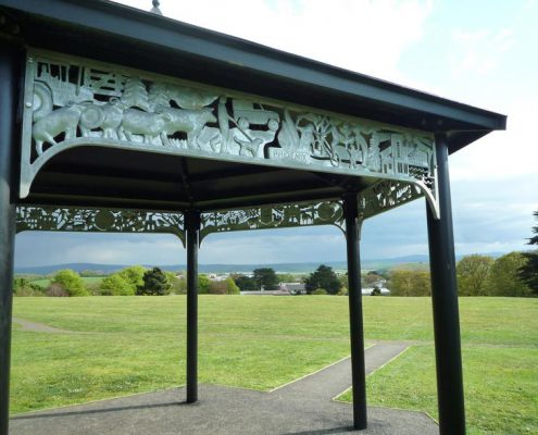 bandstand structure with relief metal imagery in park land. Made by Thrussells