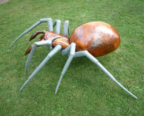 Giant Spider made of metal walking across glass lawn