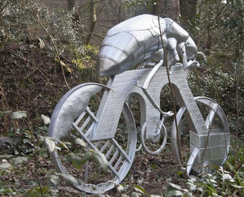 metal sculpture of a giant beetle riding a bike