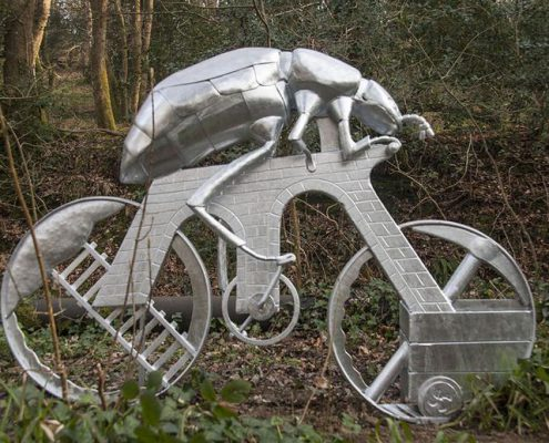 sculpture of a giant beetle riding a bike through a woodland. Made from steel by Thrussells. Plym Valley Trail. Plymouth public art