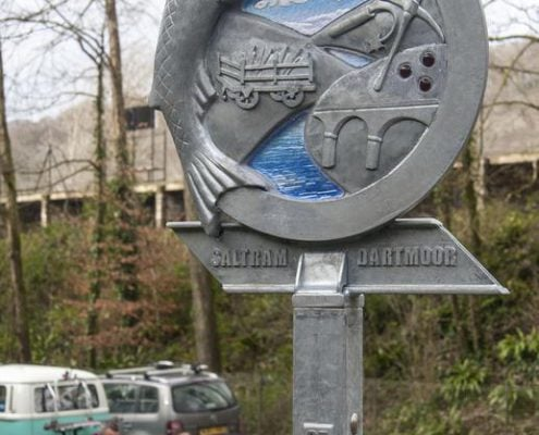 Waymarker sign made of metal and blue glass. Fish and railway themed