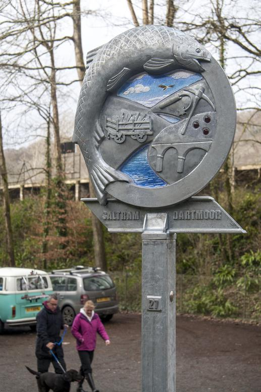 Waymarker sign made of metal and blue glass. Fish and railway themed. Plymouth public art