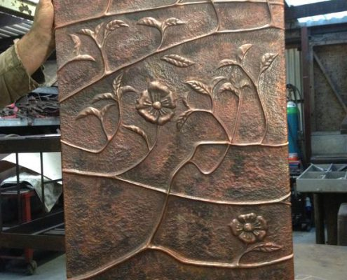 Copper Repoussé panel depicting flowers and vine. Made by Thrussells