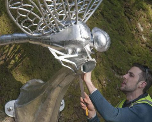 Thomas Thrussell checks over the giant metal dragonfly sculpture