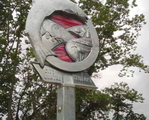 Waymarker sign made of metal and pink glass. Fish and railway themed. Plymouth public art