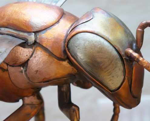 Upclose with a giant bee sculpture head and torso, made from copper and stainless steel.