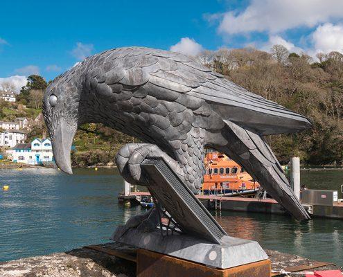 metal bird sculpture holding a book