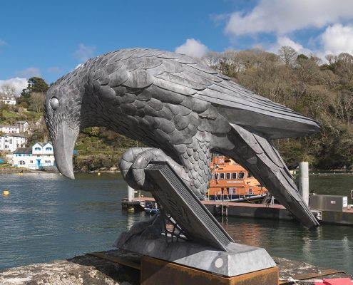 metal bird sculpture holding a book. Public Art Cornwall