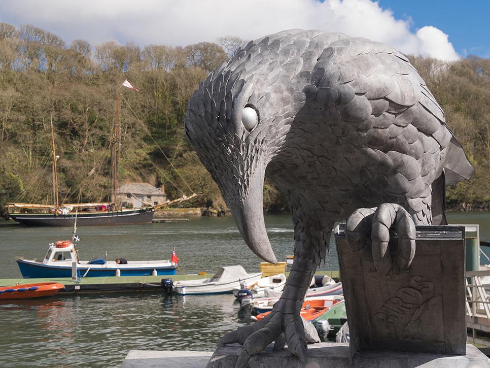 bird sculpture holding a book