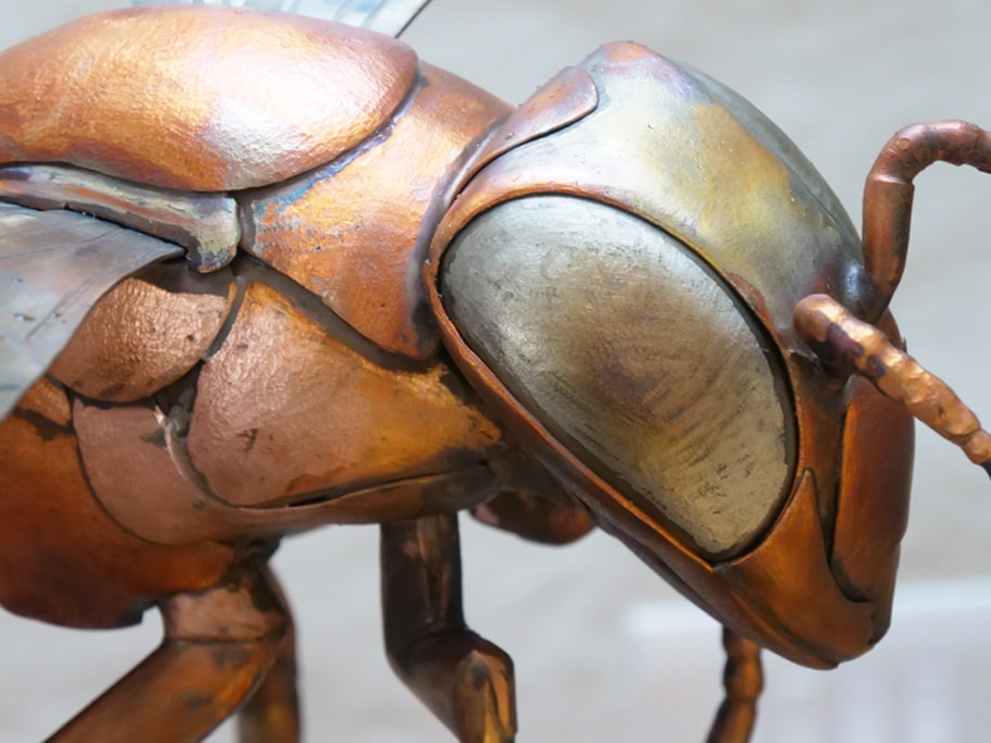 up close with a giant bee sculpture head and torso, made from copper and stainless steel.