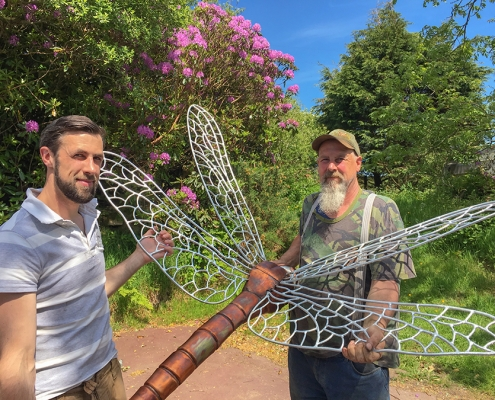 Sculptors Thomas and Gary Thrussell hold up their metal dragonfly sculpture