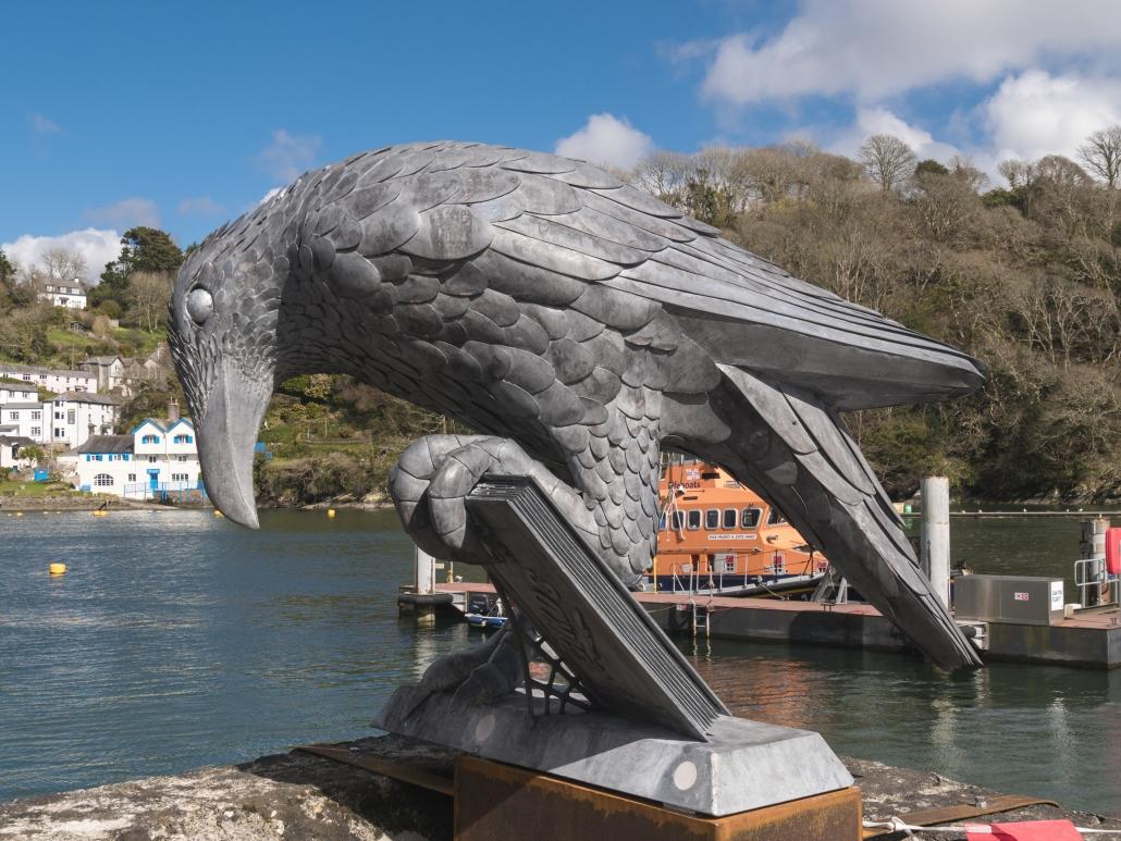 metal bird sculpture holding a book. Public Art Cornwall