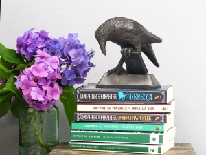 small resin statue of 'Rook With A Book' sat upon a collection flowers Daphne Du Maurier books with a vase of Hydrangeas