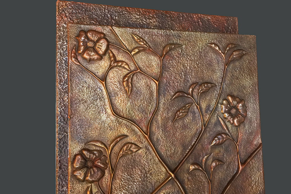 copper repousse panel depicting vine and flowers design. Made by Thrussells