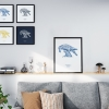 Black wooden square frame print with Thrussells cream bird on navy blue in collection in living room