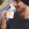 Man with white enamel mug with Thrussells yellow bird
