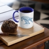 Two tone white and navy blue mug with Thrussells blue bird with coffee and cake
