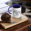Two tone white and navy blue mug with Thrussells grey bird with coffee and cake