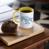Two tone white and yellow mug with Thrussells blue bird with coffee and cake