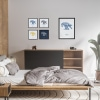 Black wooden square frame print with Thrussells cream bird on navy blue in collection in bedroom
