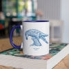 Two tone white and navy blue mug with Thrussells blue bird on book