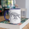 Two tone white and navy blue mug with Thrussells grey bird on book