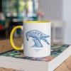 Two tone white and yellow mug with Thrussells blue bird on book
