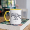 Two tone white and yellow mug with Thrussells grey bird on book