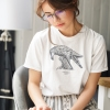 Woman reading with white t-shirt with Thrussells grey bird