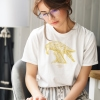 Woman reading with white t-shirt with Thrussells yellow bird