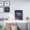 Black wooden A3 frame print with Thrussells cream bird on navy blue in living room