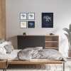 Black wooden A3 frame print with Thrussells cream bird on navy blue in collection in bedroom